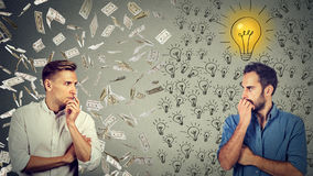 Two serious businessmen looking at each other one under money rain another with bright ideas Royalty Free Stock Photos