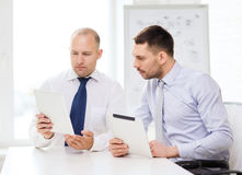 Two serious businessmen with tablet pc in office Royalty Free Stock Photography