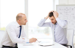 Two serious businessmen with tablet pc in office Royalty Free Stock Photos
