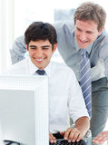 Two serious businessmen working at a computer Stock Images