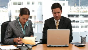 Two serious businesspeople working together. In an office stock footage