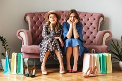 Two serious displeased tired young women shopaholics. Image of two serious displeased tired young women shopaholics sitting indoors in shop showroom with stock photo