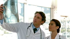 Two serious doctors looking at Xray. In slow motion stock footage