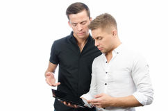 Two serious guys are working on the project. Tablet and technology. Two attractive guys in the studio. Business and education. Technology royalty free stock image