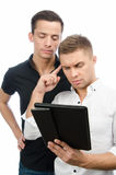 Two serious guys are working on the project. Tablet and technology. Two attractive guys in the studio. Business and education. Technology stock photos