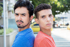 Two serious hispanic guys back to back in city royalty free stock photo