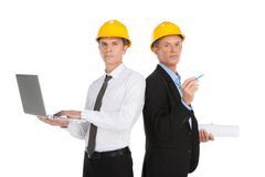 Two serious man working at site. Men wearing yellow helmet at workplace Royalty Free Stock Images