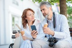 Two serious mature tourists sitting on a bench in a city, eating ice cream and talking stock images