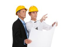 Two serious older man standing. Engineer showing foreman building plan Stock Photography
