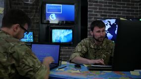 Two serious soldiers in uniform, War center, monitoring room, working for laptop, search safety system stock video footage