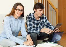 Two serious student preparing for exam together. On sofa in home royalty free stock photos