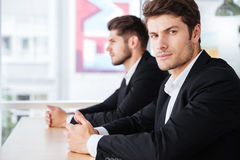 Two serious young businessmen sitting in office Stock Photos