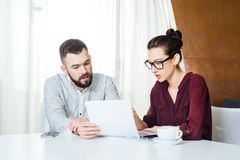 Two serious young businesspeople working together on business meeting Stock Images