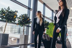 Two serious young female colleagues walking through airport passageway carrying suitcases.  Stock Photo