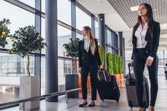 Two serious young female colleagues walking through airport passageway carrying suitcases stock photography