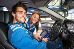 Two service mechanics, running a diagnostics program inside a ve. Two service mechanics, reading out a car's software, and running a diagnostics program on a Royalty Free Stock Images