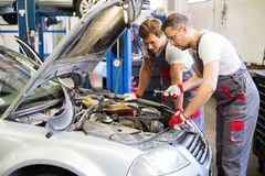 Two servicemen in a car workshop stock photo