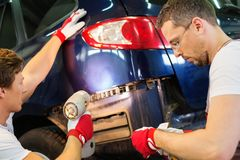 Two servicemen in a car workshop Royalty Free Stock Photos