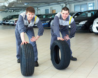 Two servicemen repairmen automobile mechanic with two tires. Two servicemen repairmen automobile mechanic with two car tires Royalty Free Stock Images