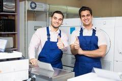 Two servicemen smiling at shop Royalty Free Stock Photos