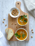 Two servings of soup, two slices of bread on a cutting board. Royalty Free Stock Images