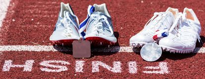 Two sets af running spikes at finish line with medals stock image