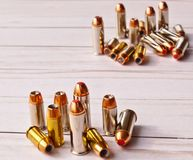 Two sets of 40 caliber bullets and 44 special bullets on a white wooden background. The set in the background is slightly blurred, spotlighting the one in the royalty free stock photos