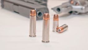 Two sets of different bullets with a revolver and a pistol in the background. Four bullets, two 9mm and two .357 magnum with a stainless .357 revolver and a royalty free stock photo