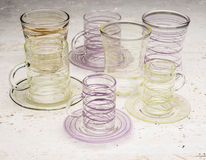 Two Sets of Drinking Glasses with Yellow and Purple Streaks royalty free stock photos
