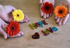 Two sets of hands holding multi colored flowers Stock Photos