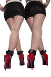 Two sets of red heels, legs and cuffed ankles. Stock Photo