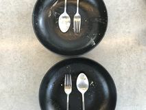 """Two sets of silver spoon, fork and plate which finished eating. On gray cement bonded particle board, shot from top view, """"delicious meal"""" concept Royalty Free Stock Images"""