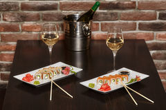Two sets of sushi rolls with chopsticks and wine glasses Stock Photo