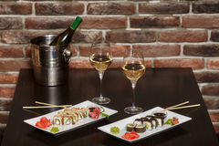 Two sets of sushi rolls with chopsticks and wine glasses Royalty Free Stock Image