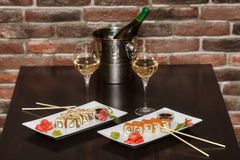 Two sets of sushi rolls with chopsticks and wine glasses Royalty Free Stock Photography