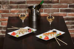 Two sets of sushi rolls with chopsticks and wine glasses Royalty Free Stock Photos