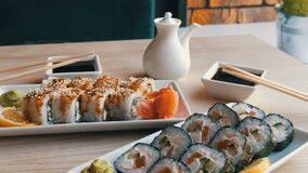 Two sets of sushi rolls in a stylish, beautifully decorated cafe. Restaurant Japanese cuisine on the table next to sushi. Two sets of sushi rolls in a stylish stock video