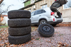 Two sets of winter wheels and tyres ready for replacement at car, copyspace Stock Photos