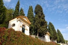 Two of the seven churches, walls covered with capers and large cypresses in Monselice through the hills in the Veneto (Italy) Stock Image