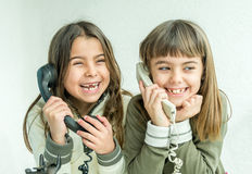 Two seven year old girls talking on the old vintage phones with. Two seven year old girls are talking on the old vintage phones with the white background Stock Photos