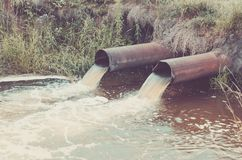 two sewer pipes pour out to the river/Industrial Pipe Dumping Waste Water Into The river. Toned royalty free stock image