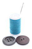 Two sewing buttons and spool of thread on white background Royalty Free Stock Photos
