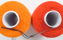 Two sewing spools with a needle. Close up of two sewing spools with a needle Royalty Free Stock Photos