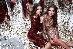 Two sexy beautiful woman wear skinny gold red dress shiny sequin. Two sexy beautiful women wear skinny gold red dress shiny sequins style party celebrate New Stock Photo