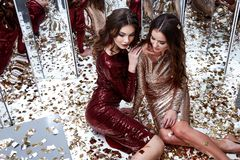 Two sexy beautiful woman wear skinny gold red dress shiny sequin Royalty Free Stock Photography