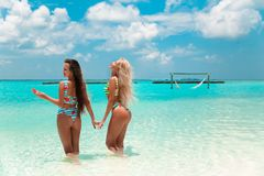 Two sexy bikini models having fun on tropical beach, exotic Maldives island. Summer vacation. Happy smiling women in fashion
