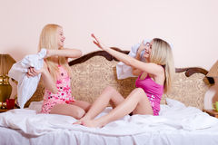 Two blonde girls having fun fighting pillows on the bed on light copy space background above them Royalty Free Stock Images