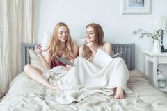 Two blonde girls in pyjamas having fun in the bedroom. Young females lying in bed using tablet. Two blonde girls in pyjamas having fun in the bedroom. Young stock photos