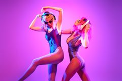 Two DJ girl with Dyed Hair dance. Art music. Two DJ girl in party outfit dance. Colorful neon mixed light. Rave house music vibes. High Fashion. Model women with royalty free stock image