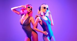 Two DJ girl with Dyed Hair dance. Art music. Two fashionable DJ girl in party outfit dance. Colorful neon uv mixed light. Rave house music vibes. Model women stock images